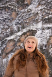 Smiling woman outdoors among snow-capped mountains looking up Stock Photography