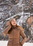 Smiling woman outdoors among snow-capped mountains looking up Stock Image