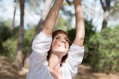 Smiling woman outdoors in woodland. Looking up at her raised hands which are off screen Stock Photo