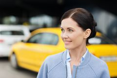 Smiling woman over taxi station or city street Stock Images