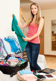 Smiling woman  packing clothes into suitcase. Smiling woman with long hair packing clothes and accessories into suitcase Stock Photo