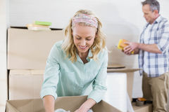 Smiling woman packing mug in a box Royalty Free Stock Images