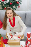 Smiling woman packing parcel with Christmas gift Royalty Free Stock Image