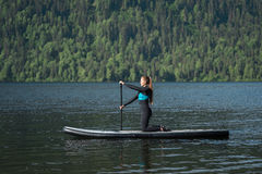 Smiling woman paddleboarding on knees at the mountain lake Royalty Free Stock Images