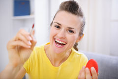 Smiling woman painting on Easter egg Stock Image