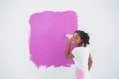 Smiling woman painting her wall in bright pink Stock Image