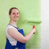 Smiling woman painting with paint roller Stock Photo