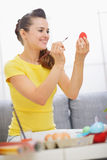 Smiling woman painting on red Easter egg Stock Photo