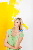 Smiling woman painting with roller Stock Photography