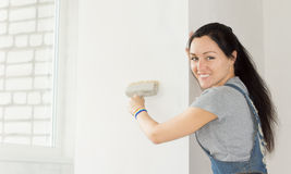 Smiling woman painting a section of wall Royalty Free Stock Photo