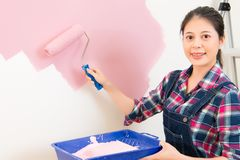 Smiling woman painting wall at home Stock Photography