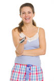 Smiling woman in pajamas holding TV remote control Stock Photography