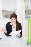 Smiling woman with papers on table Stock Photo