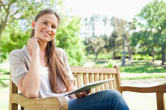 Smiling woman on a park bench with her tablet computer Stock Image