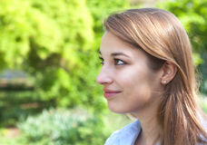 Smiling woman in a park looking to the left Royalty Free Stock Image