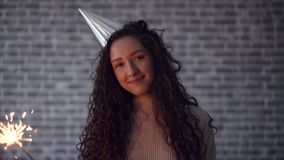 Smiling woman in party hat holding bengal light dancing on brick background. Smiling young woman in party hat is holding bengal light dancing on brick background stock video footage