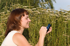 Smiling woman with PDA. In a meadow Stock Photography