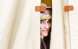 Smiling woman peeping behind tent Royalty Free Stock Photo