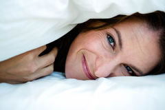 smiling woman peering  out from under a duvet Royalty Free Stock Image