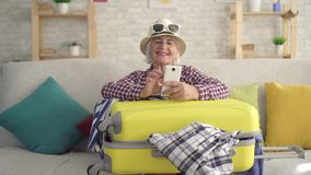 Smiling old woman in a hatuses a smartphone with a suitcase for travel in his hands sitting on the couch. Smiling woman pensioner in a hatuses a smartphone with stock video