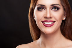 Smiling woman with perfect make up and teeth on black background Royalty Free Stock Photo
