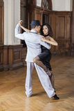 Smiling Woman Performing With Male Tango Dancer. Portrait of smiling women performing with male tango dancer in restaurant Stock Image