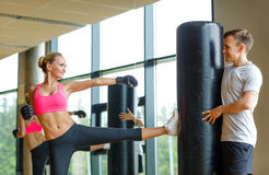 Smiling woman with personal trainer boxing in gym Royalty Free Stock Photos
