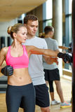 Smiling woman with personal trainer boxing in gym Stock Images
