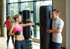 Smiling woman with personal trainer boxing in gym Stock Photos