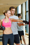 Smiling woman with personal trainer boxing in gym Royalty Free Stock Image