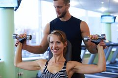 Smiling woman and personal trainer exercising in gym stock images