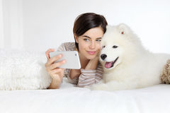 Smiling woman with pet dog. selfie. Selfie, smiling woman with pet dog lying in bed Stock Photography