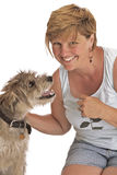 Smiling woman pets cute shaggy dog. Happy smiling woman pets her small friendly shaggy dog. Informal posed, she wears a sleeveless top and shorts. Isolated on Stock Images