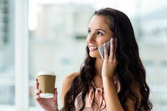 Smiling woman on phone call holding disposable cup Stock Images
