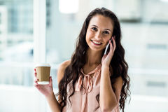 Smiling woman on phone call holding disposable cup Royalty Free Stock Images