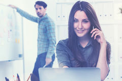Smiling woman on the phone and a man in office Stock Images