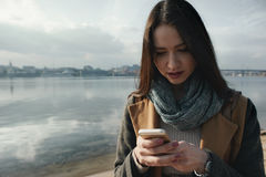 Smiling woman with the phone near the river Royalty Free Stock Photos