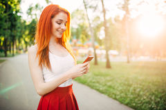 Smiling woman with phone outdoor in park on sunset Royalty Free Stock Photography