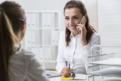 Smiling woman on the phone is taking notes. Smiling businesswoman is talking on her smartphone, taking notes and looking at her colleague sitting with her back Stock Photos