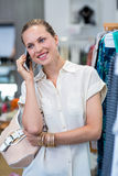 Smiling woman phoning next to clothes rail Stock Images