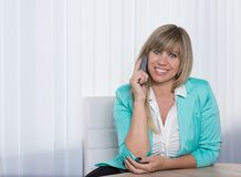 Smiling Woman is phoning in the office. Smiling businesswoman is phoning while sitting at a table in the office. The woman is looking to the camera Royalty Free Stock Photo