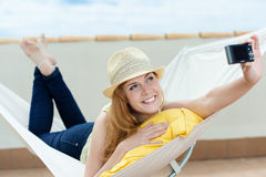 Smiling Woman Photographing Herself In Hammock Stock Photography
