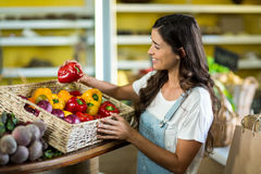 Smiling woman picking bell pepper from the basket Royalty Free Stock Photos