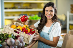 Smiling woman picking bell pepper from the basket from grocery store Stock Images