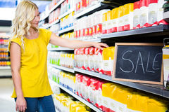 Smiling woman picking product on sale Royalty Free Stock Photography