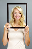 Smiling woman with picture frame Royalty Free Stock Photo