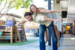 Smiling woman piggy-backing on her boyfriend Royalty Free Stock Photo