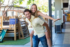 Smiling woman piggy-backing on her boyfriend Royalty Free Stock Images