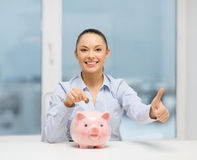 Smiling woman with piggy bank and cash money Stock Images