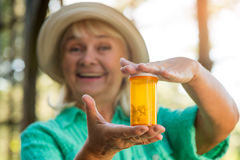 Smiling woman with pill bottle. Stock Photo